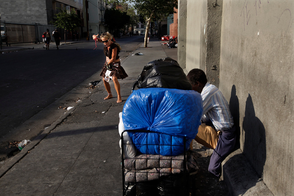 . A barefoot homeless woman sings and dances in the Skid Row area of Los Angeles, Wednesday, July 3, 2013. (AP Photo/Jae C. Hong)