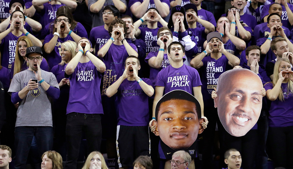 . Washington students cheer their team as they hold giant cut-out photos of C.J. Wilcox, left, and head coach Lorenzo Romar against Colorado in the second half of an NCAA men\'s basketball game Sunday, Jan. 12, 2014, in Seattle. Washington won 71-54. (AP Photo/Elaine Thompson)