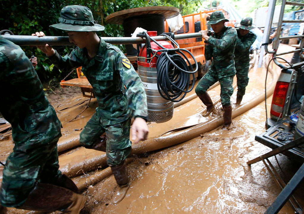 . Soldiers carry a pump to help drain the rising flood water in a cave where 12 boys and their soccer coach have been missing in Mae Sai, Chiang Rai province, northern Thailand, Friday, June 29, 2018. (AP Photo/Sakchai Lalit)
