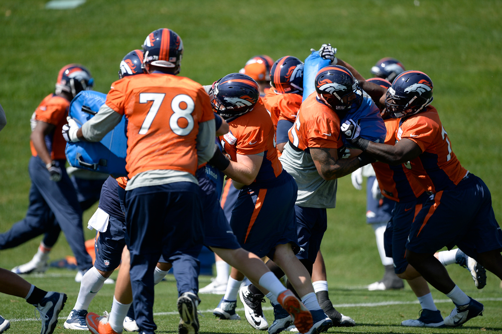 . Denver Broncos offensive line runs through drills during practice August 25, 2014 at Dove Valley.(Photo by John Leyba/The Denver Post)