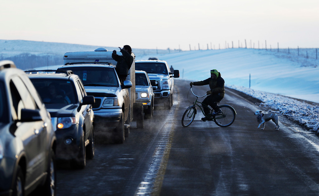 . A line of the cars wait to enter the Oceti Sakowin camp where people have gathered to protest the Dakota Access oil pipeline in Cannon Ball, N.D., Saturday, Dec. 3, 2016. (AP Photo/David Goldman)