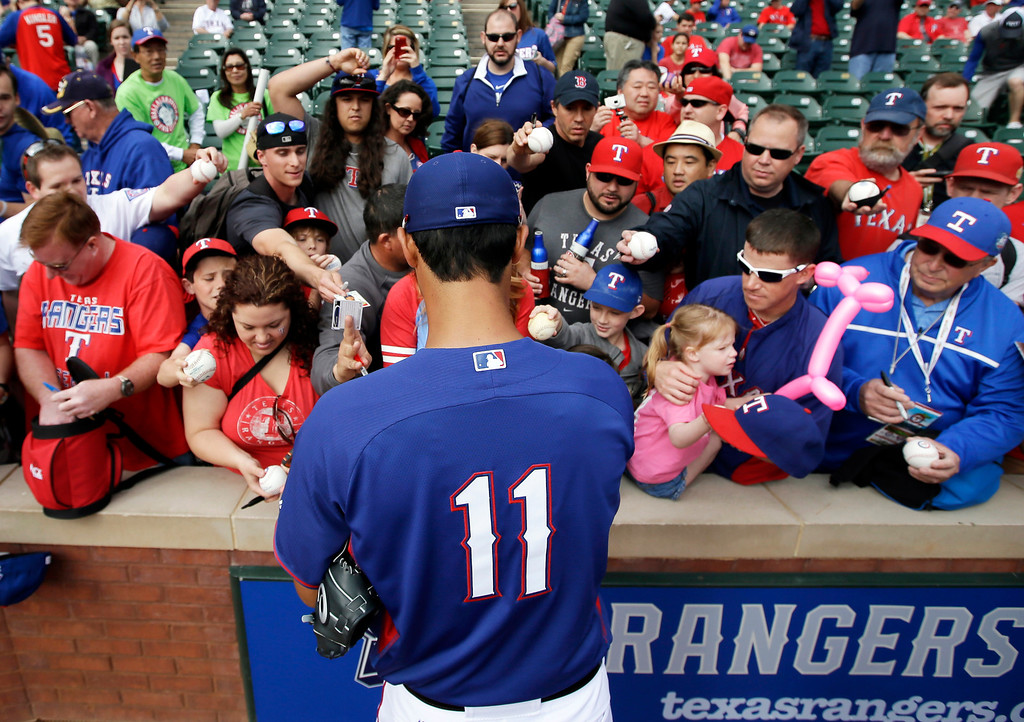. Texas Rangers\' Yu Darvish, of Japan, signs autographs for fans before a baseball game against the Philadelphia Phillies, Monday, March 31, 2014, in Arlington, Texas. (AP Photo/Tony Gutierrez)