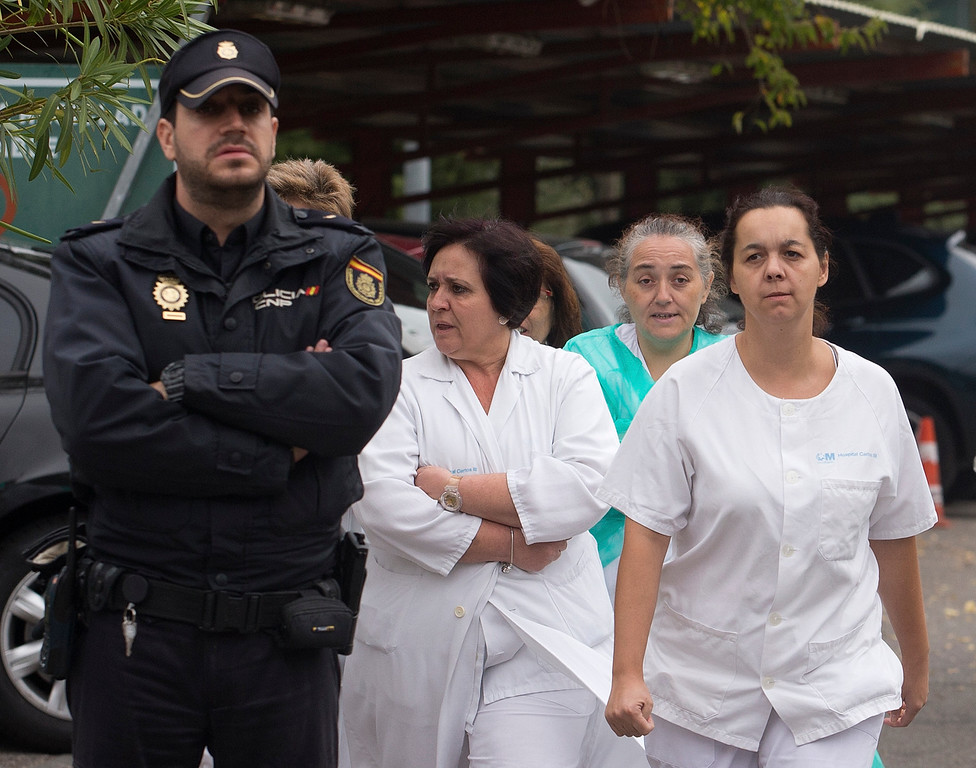 . Hospital staff walk out past police guarding the entrance to protest outside the Carlos III  hospital in Madrid, Spain, Tuesday, Oct. 7, 2014 where a Spanish nurse who is believed to have contracted the ebola virus from a 69-year-old Spanish priest is being treated after testing positive for the virus.(AP Photo/Paul White)