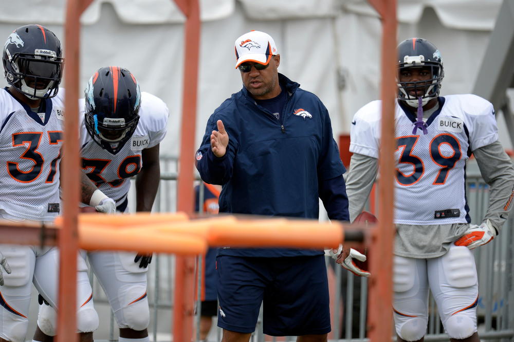 . Denver Broncos RB\'s Jeremiah Johnson (37) Montee Ball (38) C.J. Anderson (39) listen to running backs coach Eric Studesville as he explains the drill during training camp July 29, 2013 at Dove Valley. (Photo By John Leyba/The Denver Post)