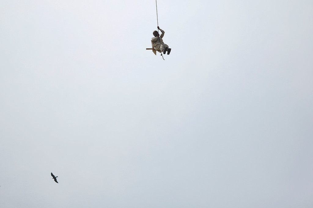 . A man is saved by a helicopter from the roof of a burning building in central Lahore May 9, 2013.    REUTERS/Damir Sagolj