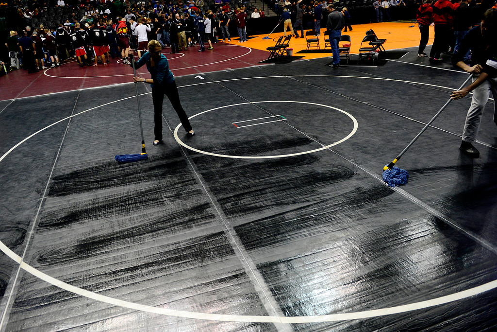 . DENVER, CO - FEBRUARY 21: Workers clean the mats during the Colorado State High School Wrestling Championships. The state finals will run through Saturday evening at the Pepsi Center. (Photo by AAron Ontiveroz/The Denver Post)