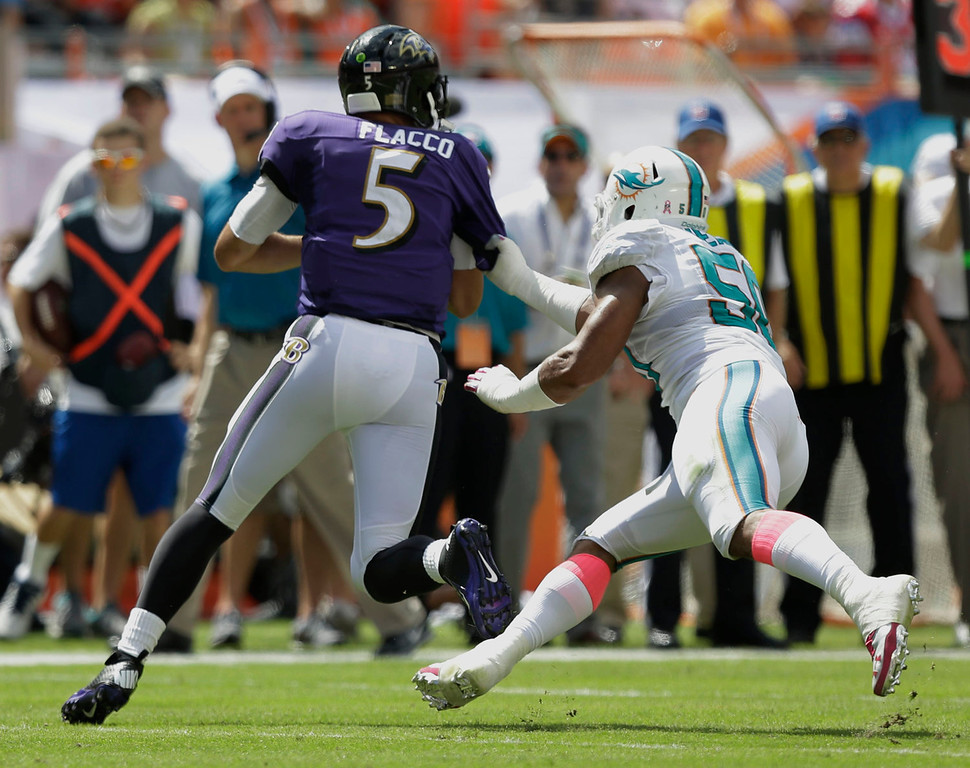 . Miami Dolphins defensive end Olivier Vernon (50) grabs Baltimore Ravens quarterback Joe Flacco (5) for a sack during the first half of an NFL football game, Sunday, Oct. 6, 2013, in Miami Gardens, Fla. (AP Photo/Wilfredo Lee)