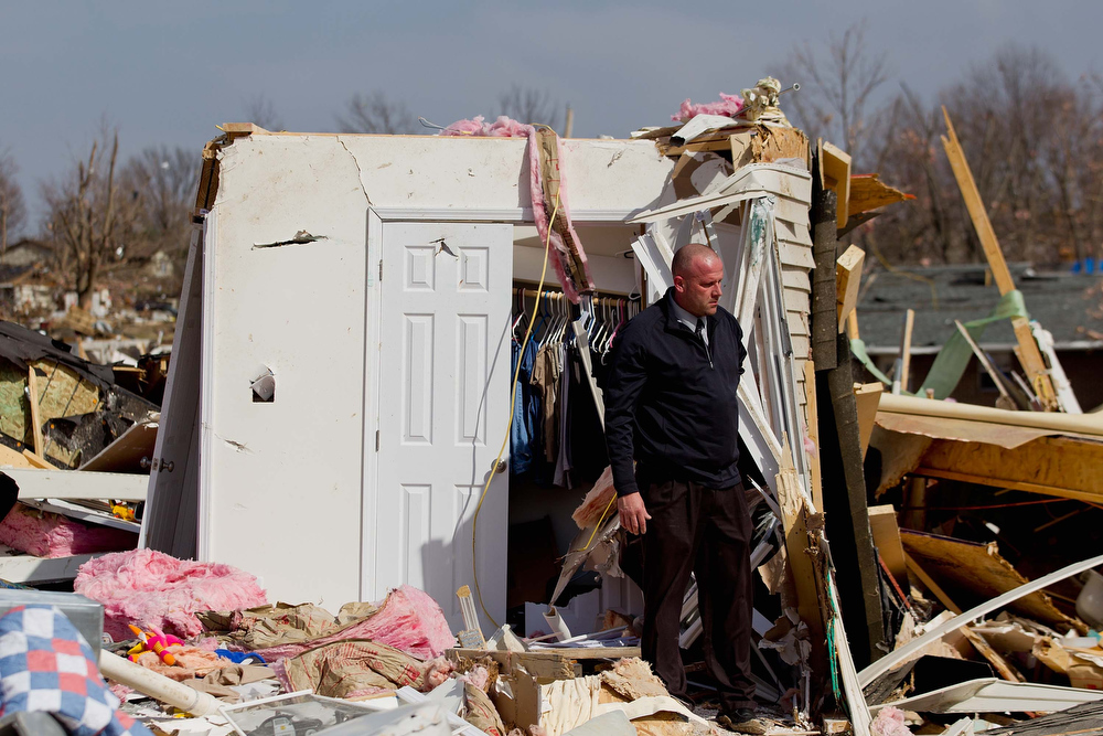 Description of . Steve McDonald stands debris from the home of his mother-in-law, Mary Osman, who was killed after a tornado touched down February, 29, 2012  in Harrisburg, Illinois. According to reports, at least nine people have died in tornadoes across the Midwest. (Photo by Whitney Curtis/Getty Images)