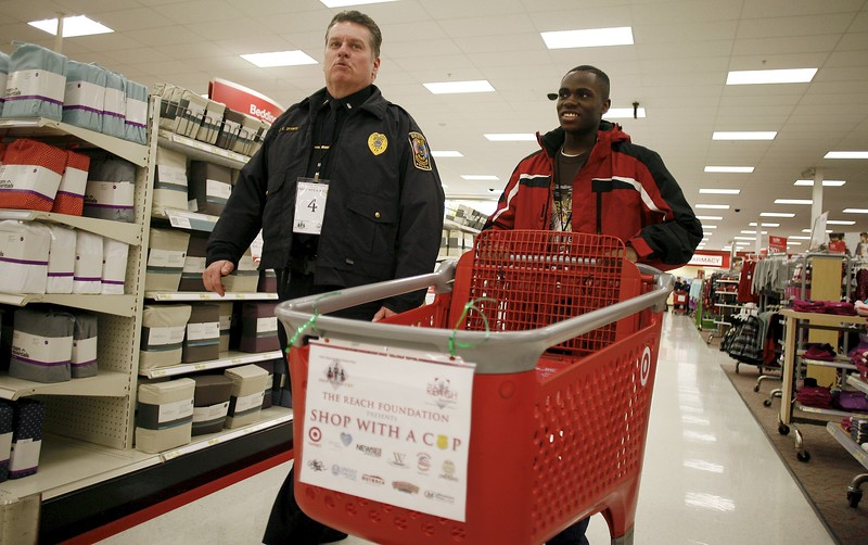 Kevin Bartram | Staff Bristol police Lt. Ed Spyros shops with Tylik Murray at Target in Southington during Shop With a Cop sponsored by the REACH Foundation on Tuesday.