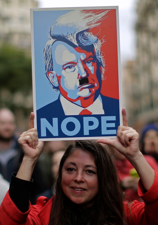 . A woman holds a cartoon depicting Donald Trump during the Women\'s March rally in Barcelona, Spain, Saturday, Jan. 21, 2017. The march was held in solidarity with the Women\'s March on Washington, advocating women\'s rights and opposing Donald Trump\'s presidency. (AP Photo/Manu Fernandez)