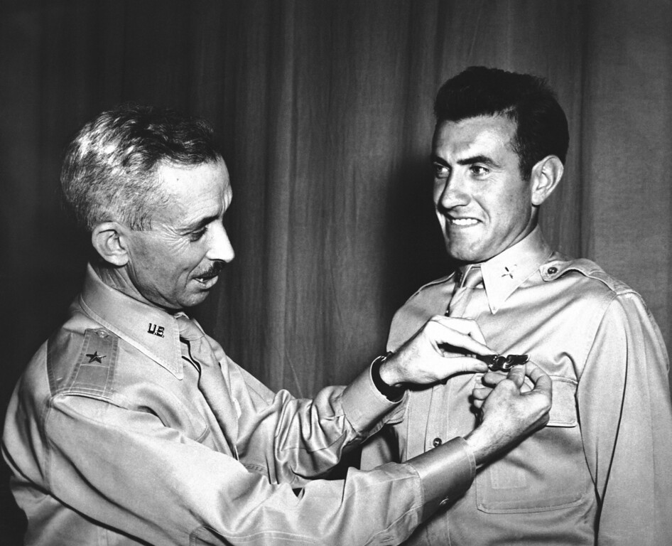 . Brig. Gen. Isaiah Davics, commanding general at Midland, Tex., Army Flying School, pins a pair of silver bombardier wings Lieutenant Lou Zamperini on August 14, 1942. In 1936 Zamperini, international track star, while in Berlin for the Olympic Games as Uncle Sam�s ace miler. (AP Photo)