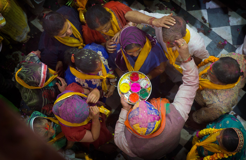 . A Hindu priest applies colors to a devotee as others wait inside Banke Bihari temple, dedicated to Lord Krishna, during Holi festival celebrations in Vrindavan, India, Wednesday, March 8, 2017. Holi, the festival of colors, celebrates the arrival of spring. (AP Photo/Manish Swarup)