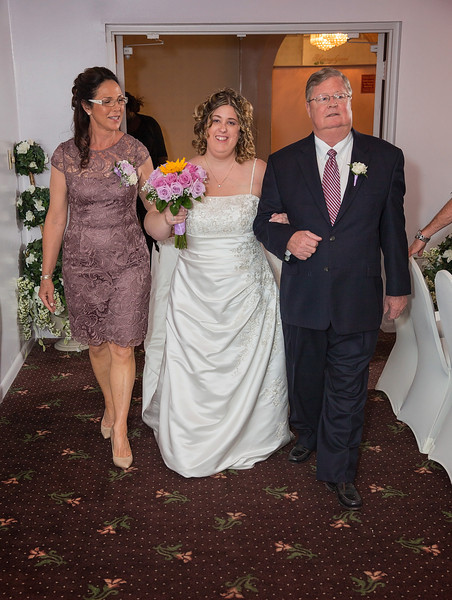 Bride walking down the aisle with parents.jpg
