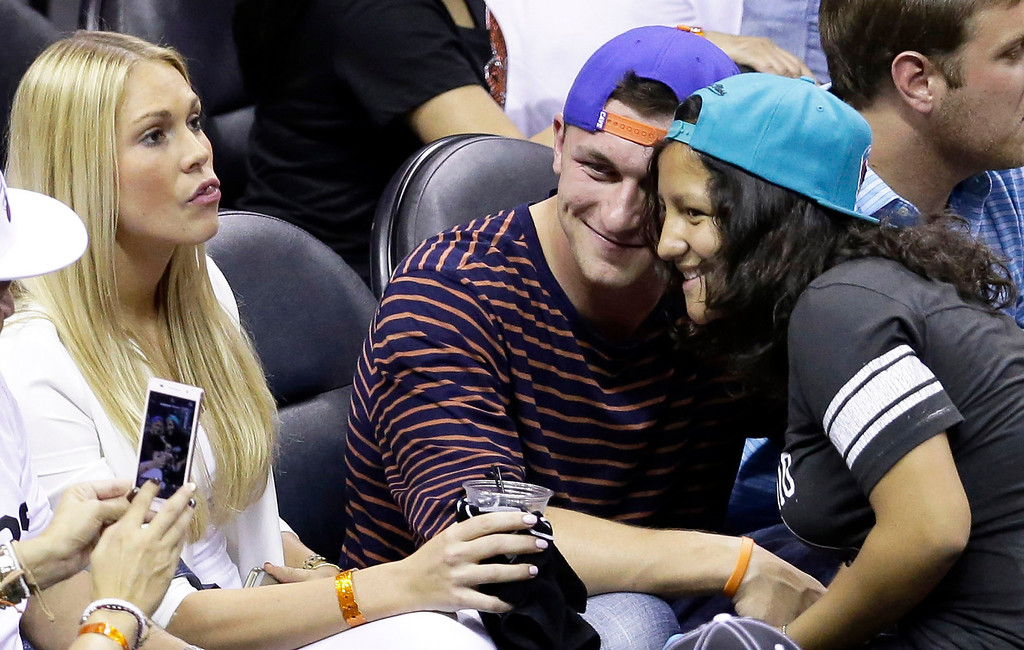 . NFL football player Johnny Manziel, center, poses for a photograph during the second half in Game 2 of the NBA basketball finals between the San Antonio Spurs and the Miami Heat on Sunday, June 8, 2014, in San Antonio. (AP Photo/Tony Gutierrez)