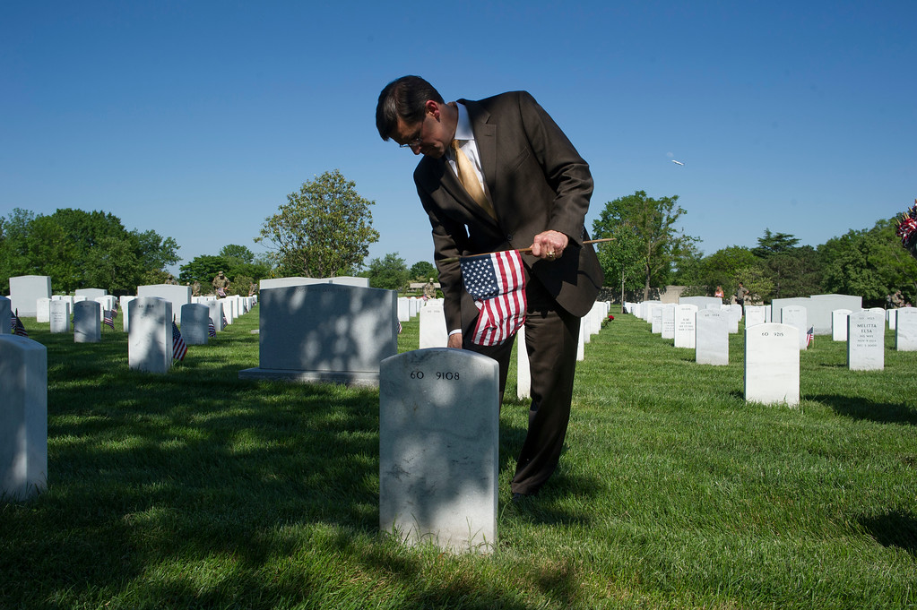 . Secretary of the Army Mark Esper places a flag at the gravesite of a fallen soldier as members of the Army 3d U.S. Infantry Regiment, The Old Guard, honor the nation\'s fallen military heroes during its annual Flags In ceremony at Arlington National Cemetery, Thursday, May 24, 2018, in Arlington, Va. (AP Photo/Cliff Owen)