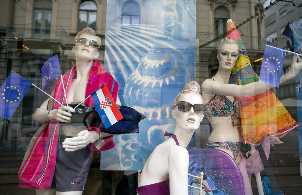 . Window mannequins with  EU and Croatian flags are on display  in a shop window in downtown in Zagreb, Croatia, Sunday, June 30, 2013. Croatia is to join the European Union on July 1, 2013. Fireworks are ready and foreign leaders are arriving as Croatia celebrated on Sunday its entry into the European Union some 20 years after winning independence in a bloody civil war that shook the continent.  Croatia will become the 28th EU member on Monday, the bloc\'s first addition since Bulgaria and Romania joined in 2007.   (AP Photo/Darko Bandic)