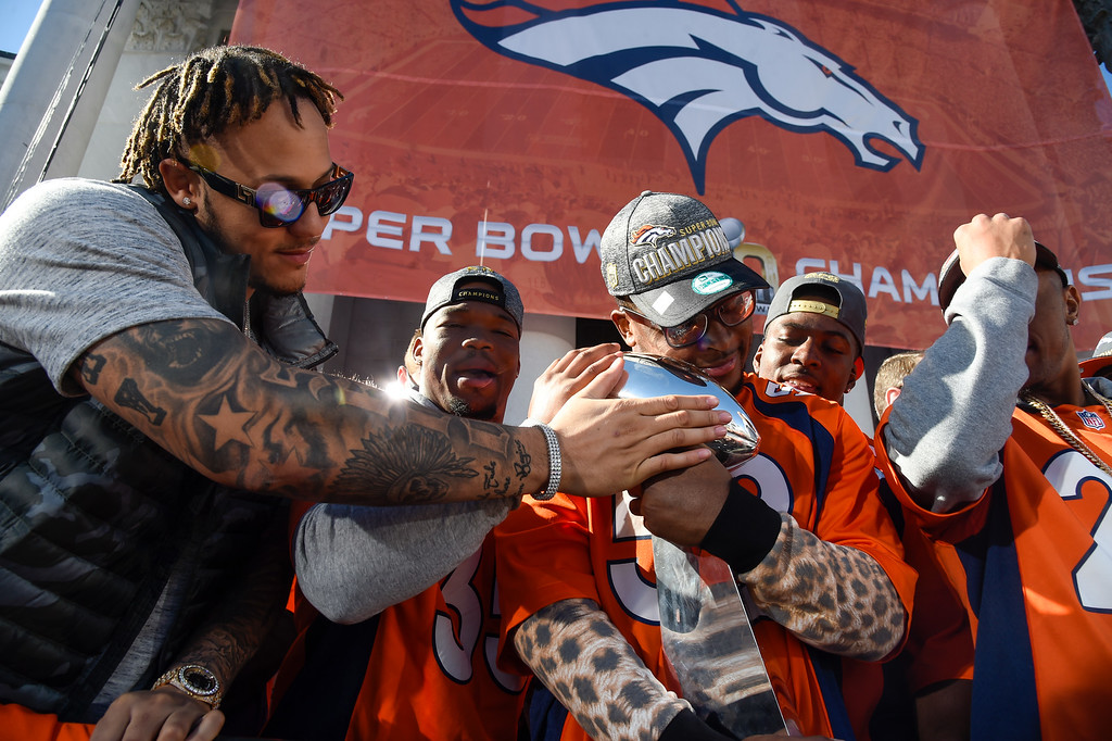 . DENVER, CO - FEBRUARY 09: Denver Broncos Shane Ray (L) Kapri Bibbs (35) touch the Super Bowl trophy as CoryNelson (52) gives it a hug on the stage during the celebration. The Denver Broncos celebrated their Super Bowl victory with a  a parade and celebration February 9, 2016 at the City & County Building. (Photo By John Leyba/The Denver Post)