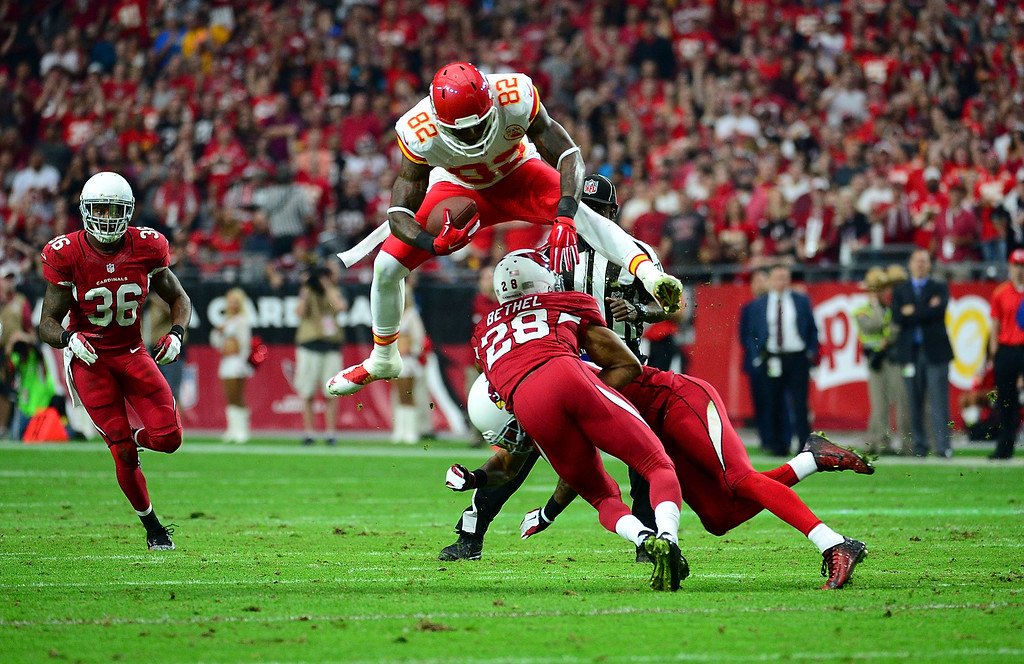 . GLENDALE, AZ - DECEMBER 07:  Wide receiver Dwayne Bowe #82 of the Kansas City Chiefs leaps over cornerback Justin Bethel #28 of the Arizona Cardinals (L) and free safety Rashad Johnson #26 (R) in the second quarter during the NFL game at University of Phoenix Stadium on December 7, 2014 in Glendale, Arizona.  (Photo by Jennifer Stewart/Getty Images)