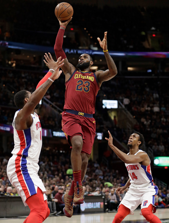 . Cleveland Cavaliers\' LeBron James, center, shoots between Detroit Pistons\' Andre Drummond, left, and Ish Smith in the first half of an NBA basketball game, Sunday, Jan. 28, 2018, in Cleveland. (AP Photo/Tony Dejak)