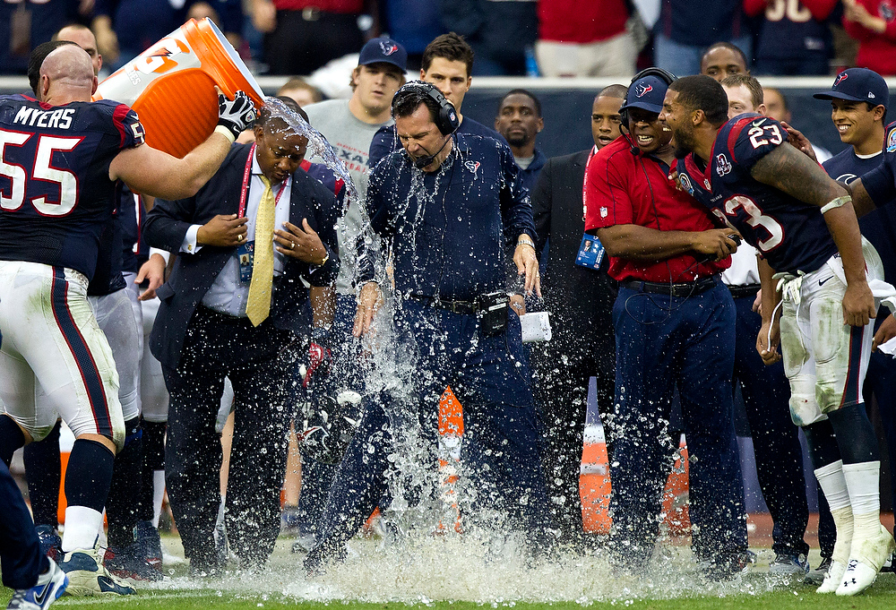 Description of . Houston Texans coach Gary Kubiak, center, is doused by Chris Myers (55) as Arian Foster (23) reacts during the fourth quarter of an NFL football game against the Indianapolis Colts, Sunday, Dec. 16, 2012, in Houston. The Texans defeated the Colts 29-17. (AP Photo/Houston Chronicle,  Brett Coomer)
