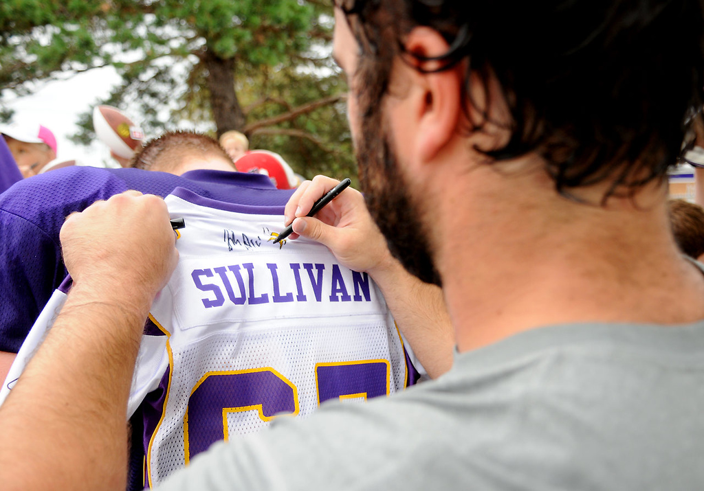 . As tight end Kyle Rudolph signs autographs for fans, center John Sullivan uses his back to sign a jersey.  (Pioneer Press: John Autey)