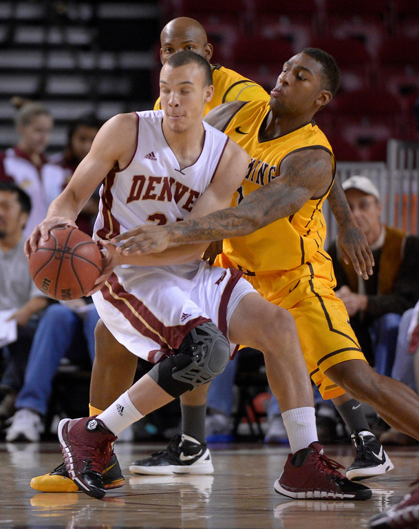 . DENVER, CO - DECEMBER 15:Wyoming Cowboys guard Charles Hankerson Jr. (1) reaches in on Denver Pioneers guard Nate Engesser (33) during the first half  December 15, 2013 Magness Arena. (Photo by John Leyba/The Denver Post)