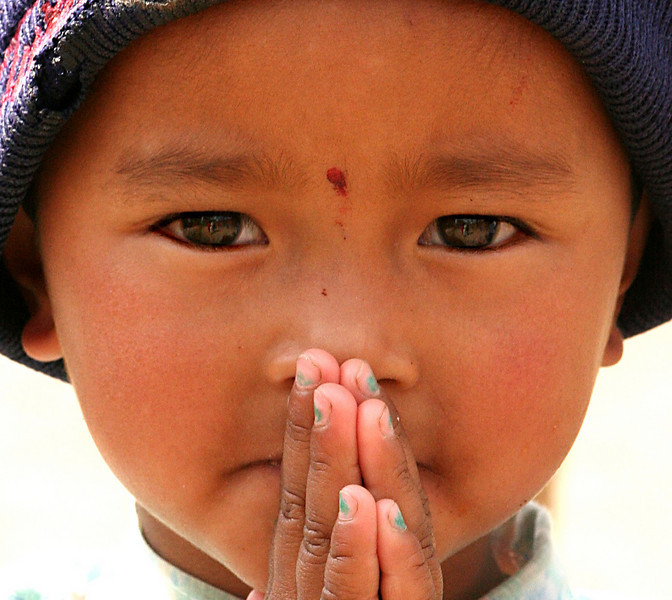 Young boy in Nepal giving the traditional greeting of Namaste..