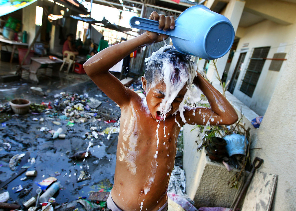 . A young Filipino takes a shower at a school turned into a temporary shelter for those affected by Typhoon Haiyan, in Tacloban, Philippines, Monday, Nov. 18, 2013. Hundreds of thousands of people were displaced by Typhoon Haiyan, which tore across several islands in the eastern Philippines on Nov. 8. (AP Photo/Dita Alangkara)