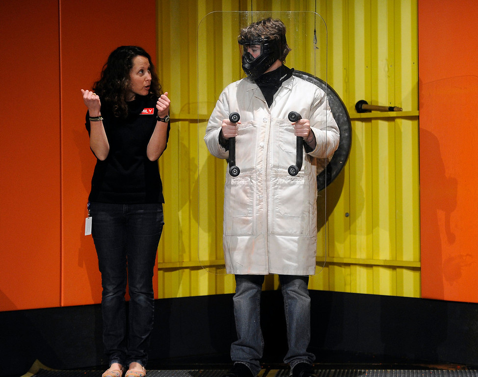 . Playing the part of a museum visitor, Andrew Parker, right, is dressed in a protective coat, mask, and shield as Emily Prengaman gives him instructions on what he must do to avoid getting hit by a paintball. The two are rehearsing their parts for running the Live-Show Dodge a Paint Ball exhibit. The Denver Museum of Nature and Science hosts MythBusters: The Explosive Exhibition which opens to the public Oct. 11 and  runs through Jan. 5, 2014. The exhibit uses interactive technology that allows visitors to spend the day as a MythBuster using the same methods as the hosts of Discovery Channel�s series MythBusters. Guest can experiment with Running in the Rain, Blind Driving, and Killer Card Toss. (Photo By Kathryn Scott Osler/The Denver Post)