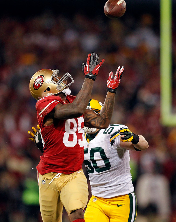 . San Francisco 49ers tight end Vernon Davis (85) catches a pass over Green Bay Packers inside linebacker A.J. Hawk (50) during the third quarter of an NFC divisional playoff NFL football game in San Francisco, Saturday, Jan. 12, 2013. (AP Photo/Tony Avelar)