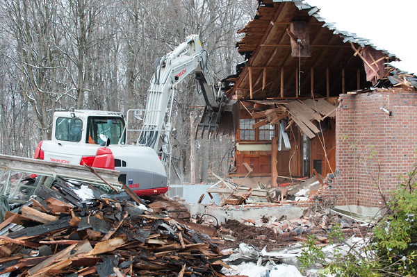 04/02/18 Wesley Bunnell | Staff Demolition of a house adjacent to Kensington Congregational Church started on Monday which is the first step in an expansion to the church property. The excavator tears into the main house area with remnants of the garage piled in front.