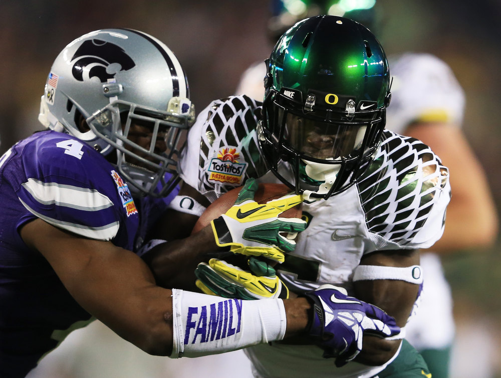 Description of . De'Anthony Thomas #6 of the Oregon Ducks tries to break the tackle of Arthur Brown #4 of the Kansas State Wildcats during the Tostitos Fiesta Bowl at University of Phoenix Stadium on January 3, 2013 in Glendale, Arizona.  (Photo by Doug Pensinger/Getty Images)