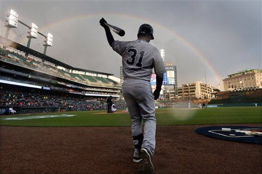 . A rainbow appears behind Comerica Park as New York Yankees\' Gregorio Petit prepares to bat during the second inning of a baseball game against the Detroit Tigers, Tuesday, April 21, 2015, in Detroit. (AP Photo/Carlos Osorio)