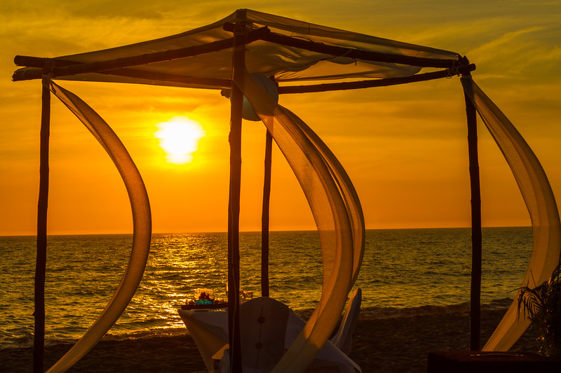A canopy and dinner table await guests for a romantic beach dinner at sunset in Puerto Vallarta, Mexico