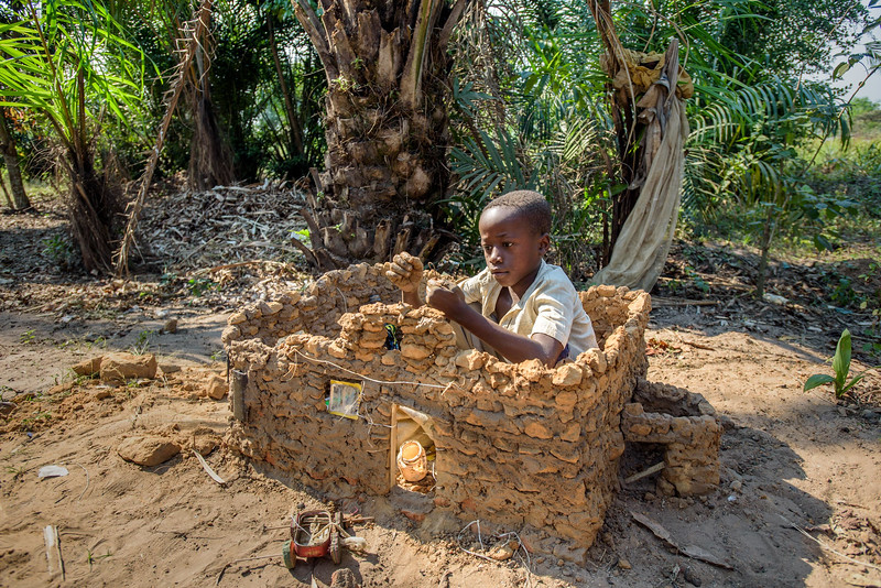 """Grace Mukoma, 10  yr-old boy, carefully builds a model house, next to his home in Central Kasai Province, DRC.  """"I'm building my house.""""      On one side of his real house, Grace is building his own little house. He pounds a chunk of red dirt until it breaks into pieces. He takes some of it and mixes it into a kind of mortar. The larger chunks he uses as bricks to construct his little house. Much like a dollhouse, Grace's house contains many treasures – broken cellphone cases, a small fan motor, a car made from a sardine can. The windows are the plastic packaging from a pack of batteries. Grace dreams of building his own full-size house someday.   """"It will have 6 rooms, including one for visitors. Everyone will be welcome. That way, I'll never be lonely.""""  Background Grace lives with his widowed mom, Mbombo Elize, sister Harriet, 7, and an extended family of relatives, including his widowed grandmother, Kapinga Godelive, 66.  Mbombo has had 4 children, the first when she was 15. 2 died during the time they had to run away because of the war. Now it's just Grace and his sister Harriet, 7.  They live in the Kasai Centrale province in a place called Katoka. It's a rural community. Grace and his family had to run when war broke out in the DRC.  His father was killed. His mother and her 4 children ran about 2 kilometers down the road from his house towards the Lualua River. They hid there for about 3 months. Unfortunately, because of a lack of food and disease, Grace's brother and a sister died. After about 3 months Grace and his family hesitantly made their way back to their house. It had been burnt and was empty. They've struggled ever since.    Here's a look at Grace's life today:  Home Life  """"Early in the morning I sweep the compound. Then I wash and if there is food I eat. Then I join my friends at the CFS."""" """"Sometimes they send me on other errands. If they need something, they send me.""""  Food Grace's family doesn't have enough food. On any given day they may or may"""