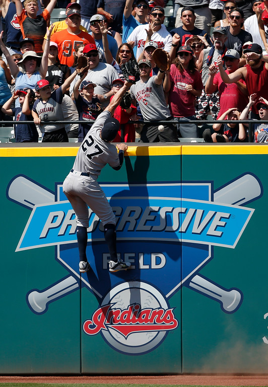 . New York Yankees\' Giancarlo Stanton (27) attempts to catch a home run by Cleveland Indians\' Michael Brantley during the eighth inning of a baseball game, Sunday, July 15, 2018, in Cleveland. (AP Photo/Ron Schwane)