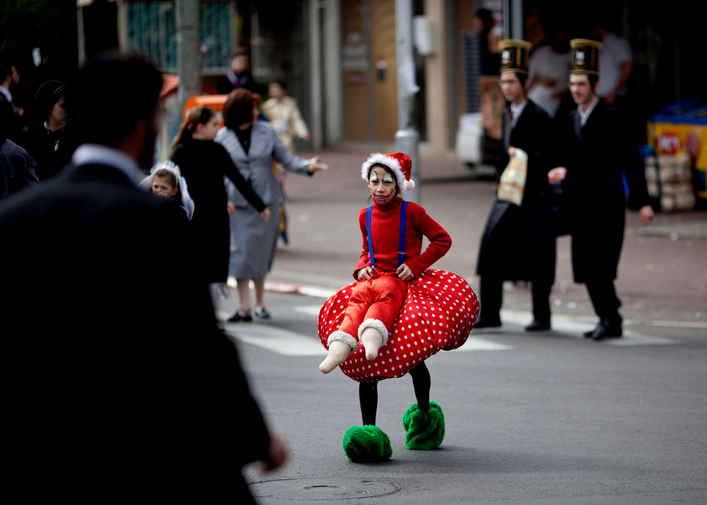 . An Ultra Orthodox Jewish girl dressed wearing a costume crosses the street during the Purim festival in the ultra-Orthodox town of Bnei Brak, Israel, Sunday, Feb. 24, 2013. The Jewish holiday of Purim commemorates the Jews\' salvation from genocide in ancient Persia, as recounted in the Book of Esther which is read in synagogues. Other customs include: sending food parcels and giving charity, dressing up in masks and costumes, eating a festive meal, and public celebration. (AP Photo/Ariel Schalit)