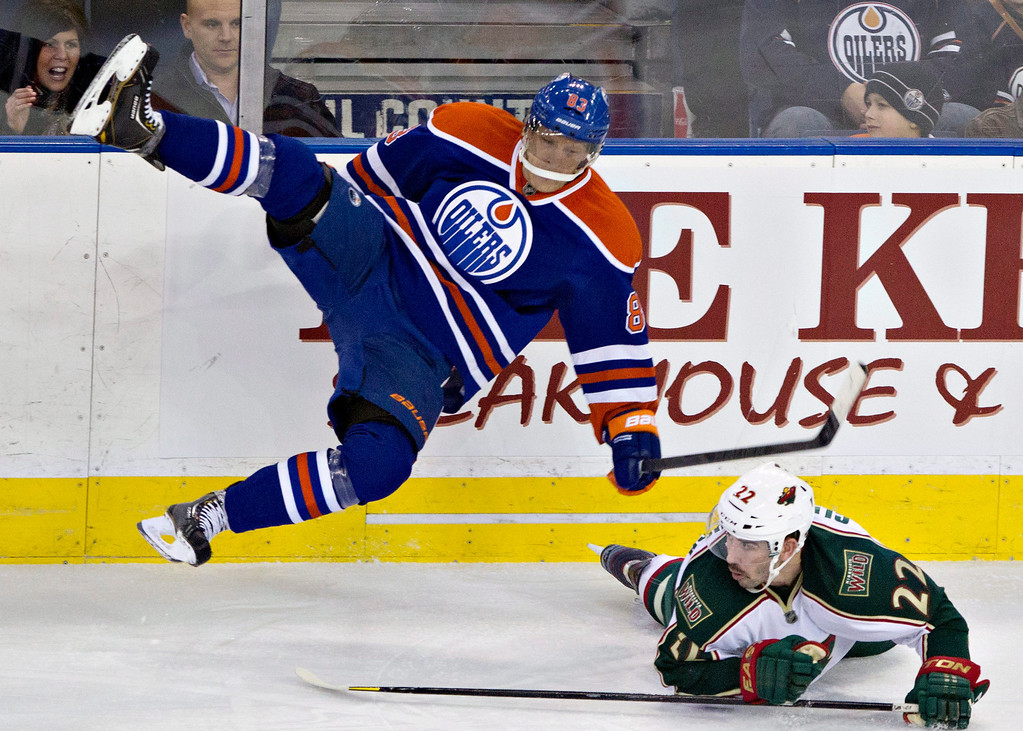 . Minnesota Wild\'s Cal Clutterbuck (22) and Edmonton Oilers\' Ales Hemsky (83) collide during third period NHL hockey action in Edmonton, Alberta, on Thursday Feb. 21, 2013. (AP Photo/THE CANADIAN PRESS,Jason Franson)