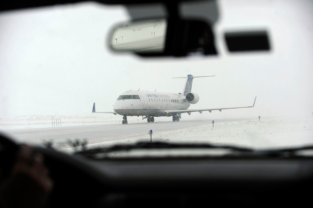 . An airplane taxis down a runway after landing at Denver International Airport on Sunday, February, 24, 2013. A major winter storm caused the cancellation of nearly 200 flights at DIA on Sunday. Seth A. McConnell, The Denver Post