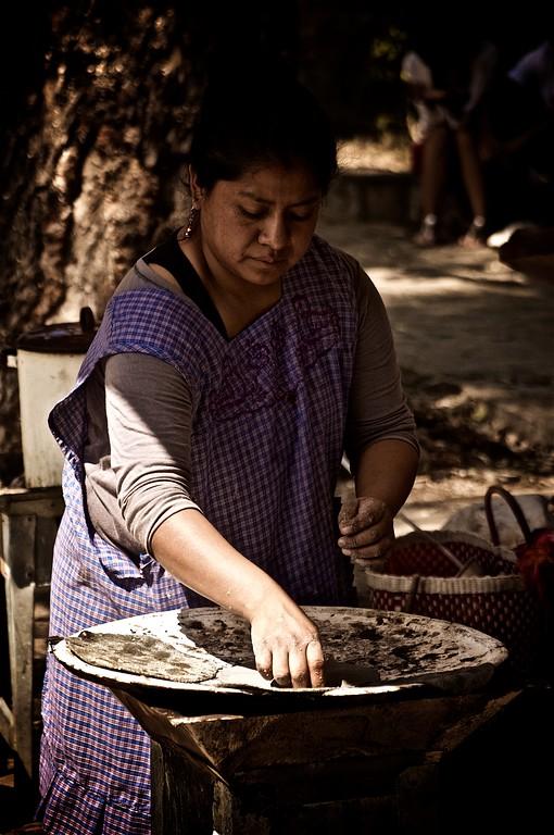 A woman prepares fresh tortillas on a clay comal in Oaxaca, Mexico.