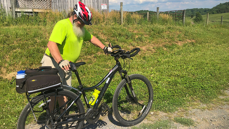 John mounting bike on Virginia Creeper Trail by barn