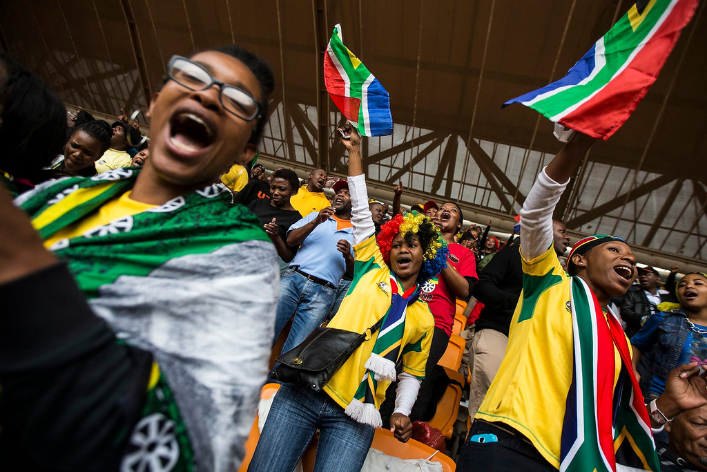 . Mourners wave South African flags as they attend the memorial service for late South African president Nelson Mandela at the First National Bank (FNB) Stadium, in Soweto, Johannesburg, South Africa, 10 December 2013. Nobel Peace Prize winner Nelson Mandela died at the age of 95 on 05 December 2013. The FNB Stadium attracted several thousand mourners and over 90 heads of state.  EPA/IAN LANGSDON