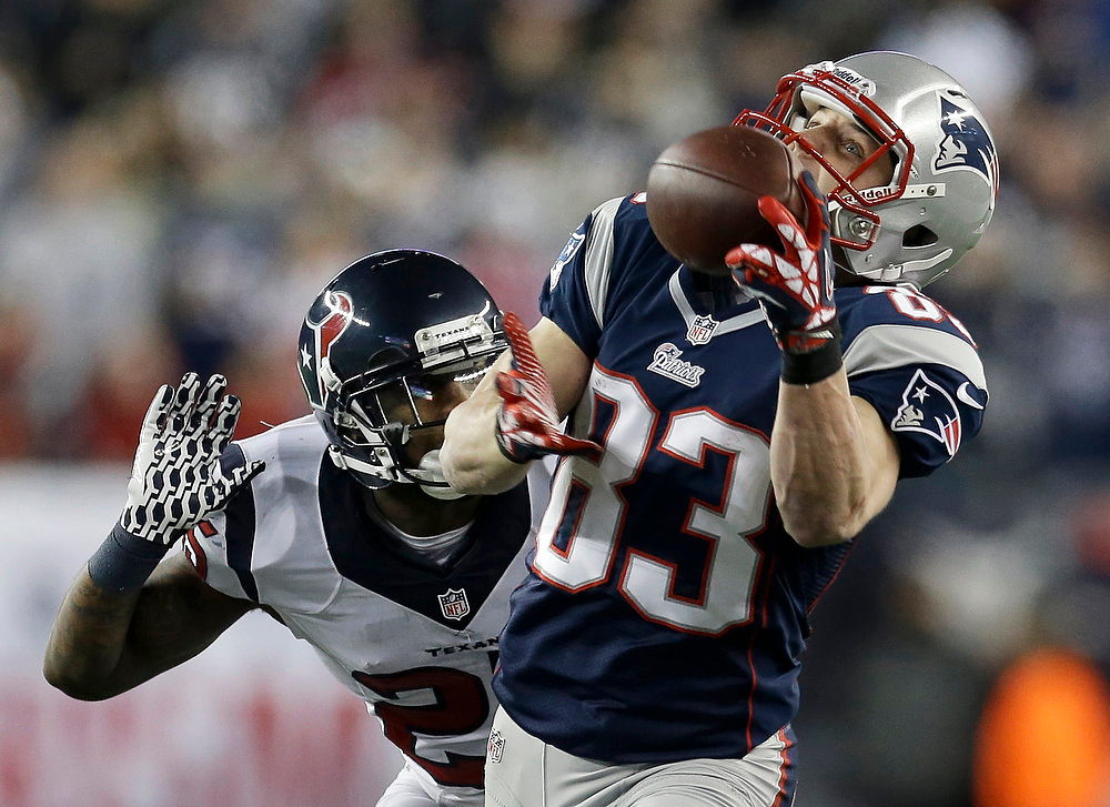 . New England Patriots wide receiver Wes Welker (83) pulls in a 47-yard pass from Tom Brady as Houston Texans cornerback Kareem Jackson chases him during the first half of an AFC divisional playoff NFL football game in Foxborough, Mass., Sunday, Jan. 13, 2013. (AP Photo/Elise Amendola)