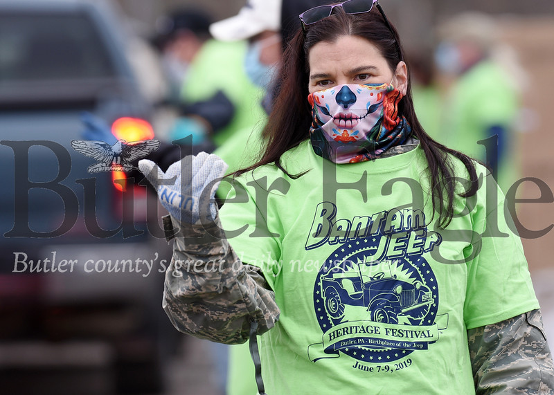 Harold Aughton/Butler Eagle: Trisha Paine, a volunteer for the Bantam Jeep groupd, directs traffic at the Butler Fair Grounds Tuesday, April 28, 2020.