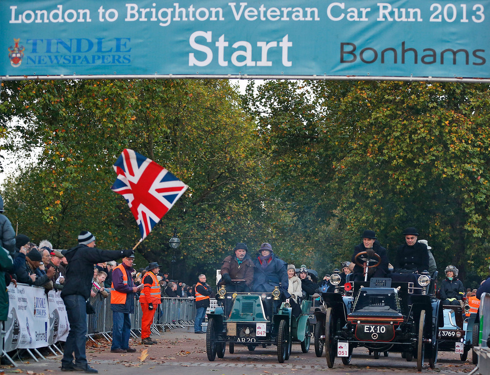 . An official waves a British flag so participants will begin the run at the start line in London\'s Hyde Park, during the London to Brighton Veteran Car Run, Sunday, Nov. 3, 2013. Over 400 pre-1905 vehicles made their way on the historic 60-mile run from Hyde Park in London to coastal Brighton in southern England, in the world\'s longest running motoring celebration spanning 117 years. (AP Photo/Lefteris Pitarakis)