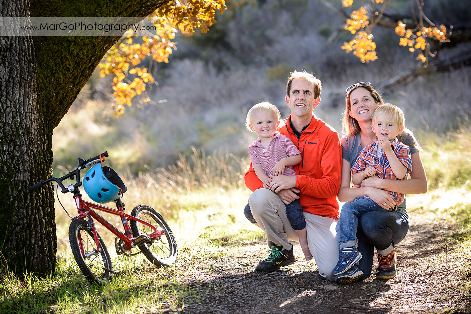 full body portrait of family of four sitting under the tree during outdoor family session at San Raeael China Camp SP