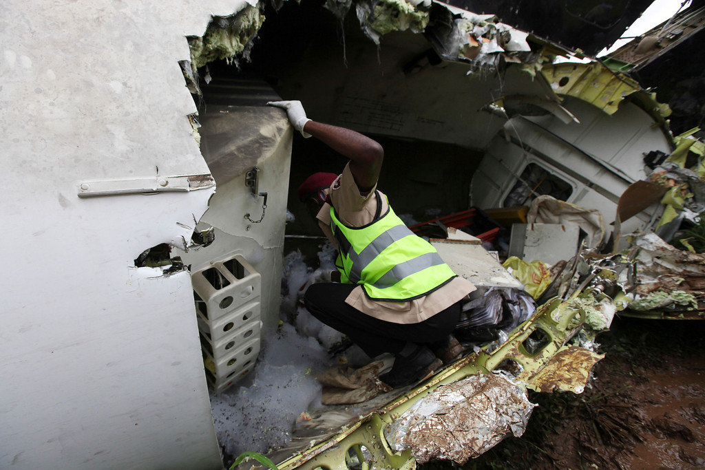 . A rescue worker inspects the wreckage of a charter passenger jet which crashed soon after take off from Lagos airport, Nigeria, Thursday, Oct. 3, 2013. Officials said there were casualties but refused to confirm reports of several deaths. (AP Photo/Sunday Alamba)