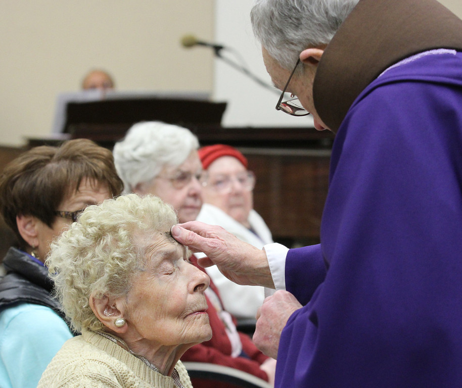 . Father Larry Dunphy, O.F.M. applies ashes to the forehead of Mary Vukas during Mass on Ash Wednesday at the Mercy Retirement & Care Center in Oakland, Calif. on Wednesday, Feb. 13, 2013.  Father Larry, a Franciscan Priest,  comes to the Senior Care Center to deliver Mass for the many seniors who are unable to travel outside of the center.  Mass is delivered every Sunday at the center where the average age is 91 years old and 90% of the residents are catholic.  During Lent, they will have Stations of the Cross prayer service every Friday at 2:00 pm. (Laura A. Oda/Staff)