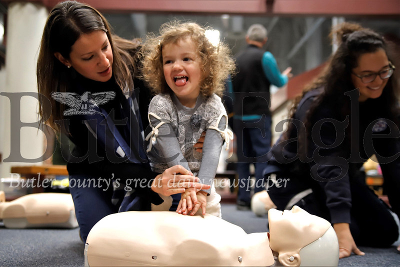 Viviana Mimran, 3, learns the basics of hands-only CPR with her mom Elissa Mimran at the Cranberry Township Municipal Center Saturday. Cranberry EMS hosted their annual Save-A-Life Saturday giving anyone in attendence a free basic CPR lesson and celebrating the lives of a few area residents who were saved by good samaritans that started CPR before EMS arrived. Elissa Mimran's father Gary Lucente was among those in attendance who were revived  by CPR after going into cardiac arrest. Lucente was in a Cranberry area shopping center when he suffered heart failure and Cranberry EMS responded. Seb Foltz/Butler Eagle