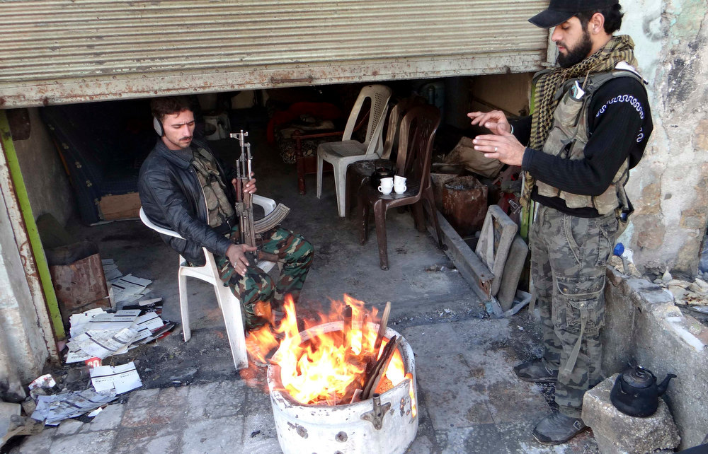 Description of . Free Syrian Army fighters warm themselves by a fire in Aleppo's al-Amereya district December 11, 2012. Picture taken December 11, 2012. REUTERS/Aaref Hretani